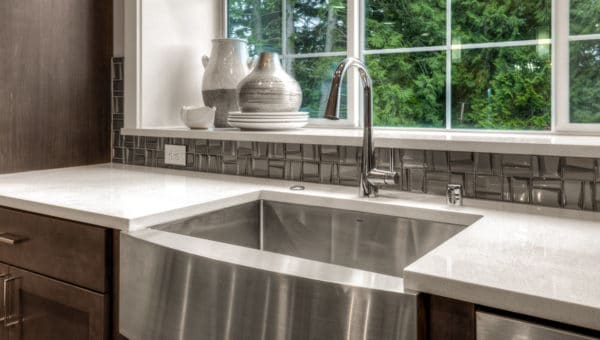 Stainless steel farmhouse-style sink in kitchen by RM Homes