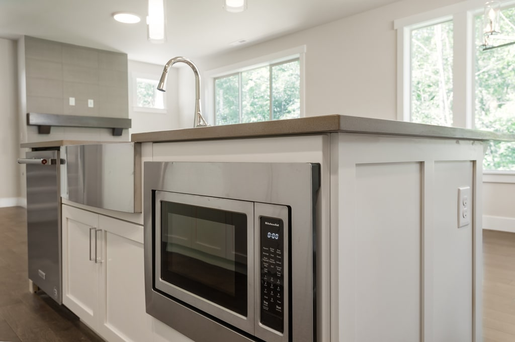 Work island contains the dishwasher, farmhouse sink and KitchenAid microwave