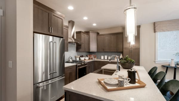 Model home kitchen work island with quartz countetops and pendant lights above