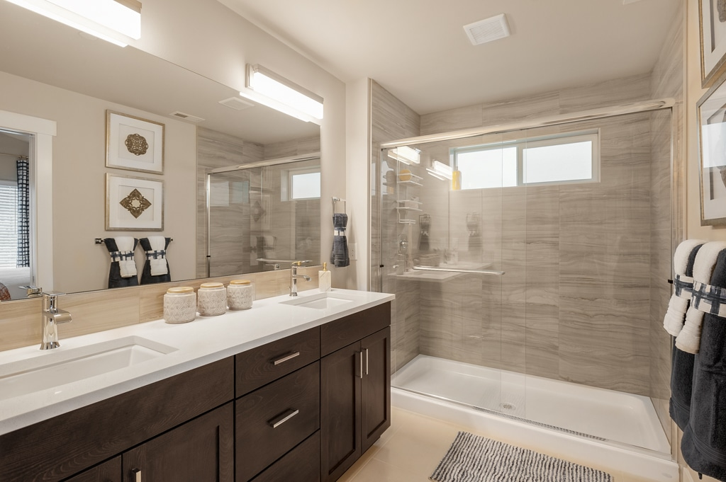 Master bath with dual-sink slab quartz topped vanity. Walk-in shower has full height tile surround and privacy glass windows.