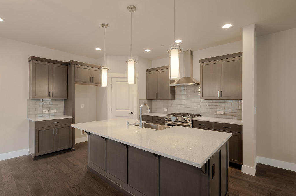 Kitchen has large work island topped with slab quartz with pendant lights above