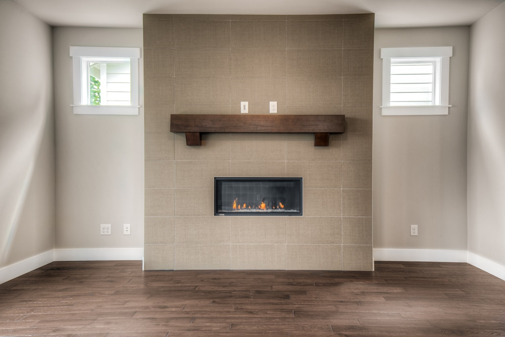 Gas fireplace has floor-to-ceiling tile surround