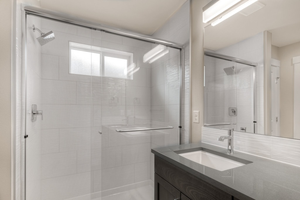 Full-height tile and opaque privacy glass window in master shower